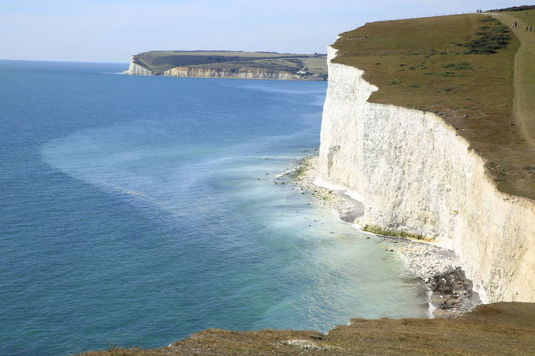 Scenic view of cliffs and sea against sky