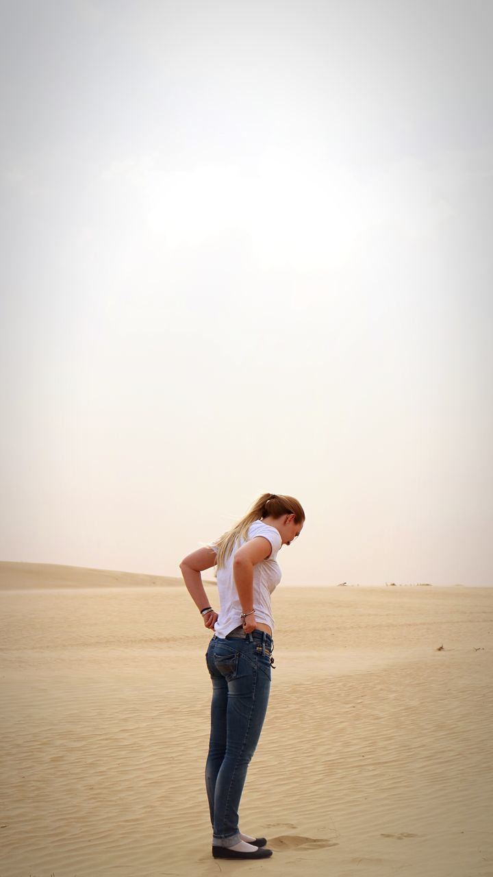 casual clothing, sand, standing, full length, one person, rear view, clear sky, nature, young adult, young women, leisure activity, landscape, sky, beauty in nature, real people, scenics, beach, day, outdoors, sand dune, adult, people