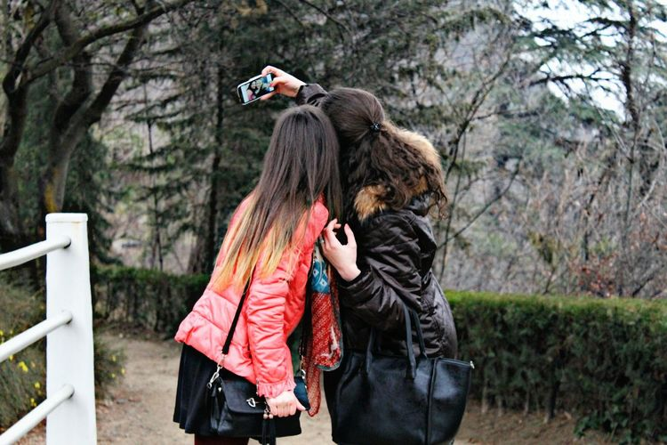 Rear View Of Friends Taking Self Portrait While Standing On Footpath