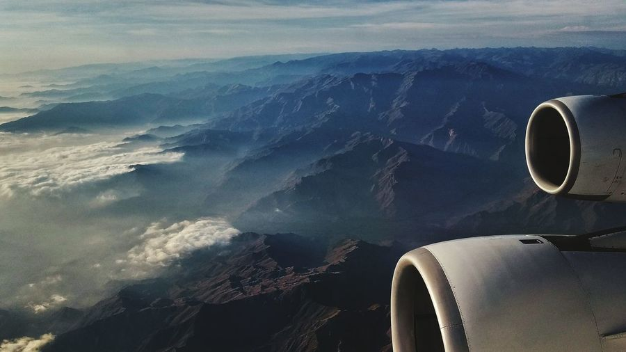 Cropped image of airplane flying over mountains