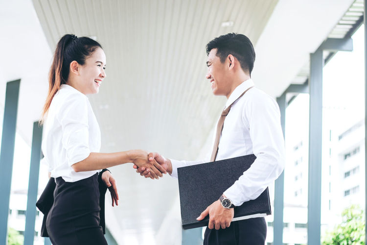 Adult Architecture Business Business Person Businessman Communication Cooperation Coworker Greeting Handshake Males  Men Occupation Outdoors Partnership - Teamwork Side View Smiling Standing Teamwork Three Quarter Length Togetherness Two People Well-dressed Women Young Adult