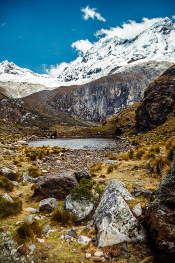 Scenic view of stream by snowcapped mountains against sky
