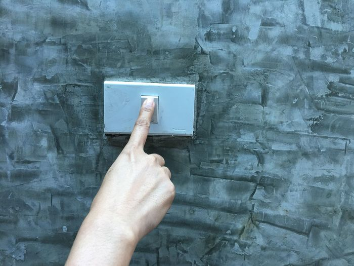 Close-up of cropped hand pressing light switch on wall