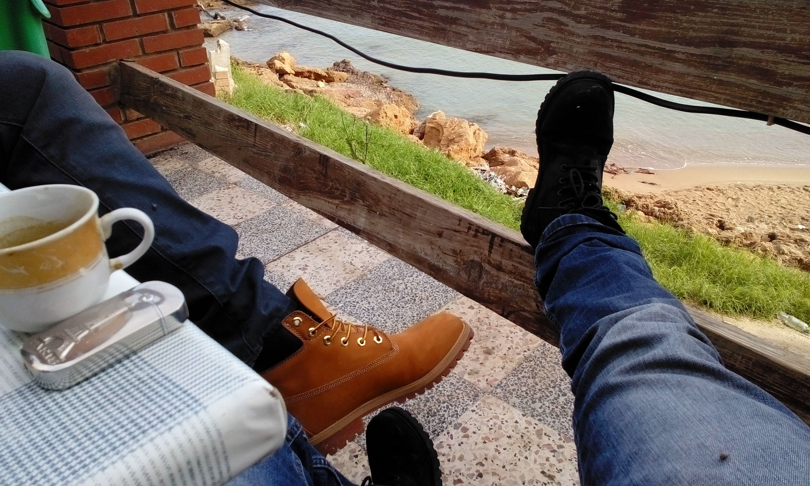 low section, person, shoe, personal perspective, lifestyles, human foot, high angle view, men, footwear, leisure activity, standing, water, sunlight, jeans, relaxation, sitting