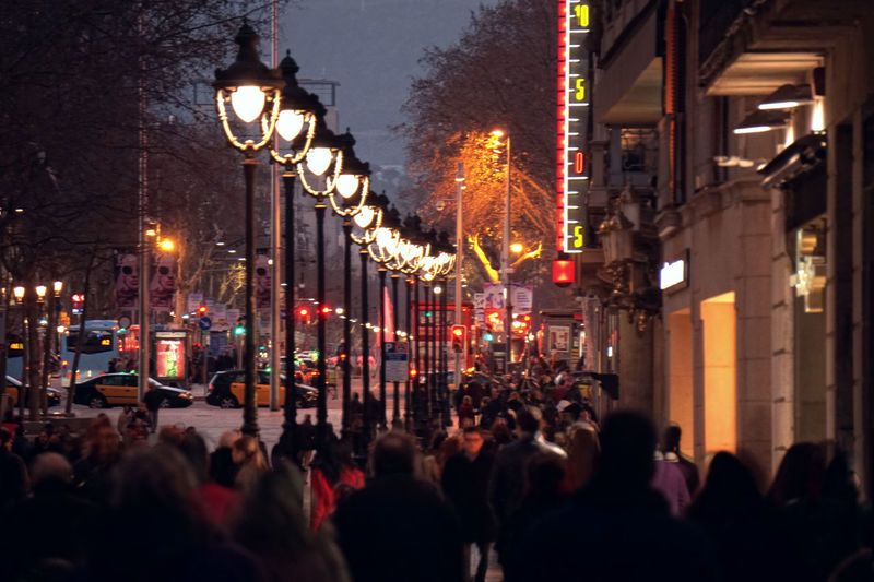 Crowded People In City Street During Dusk