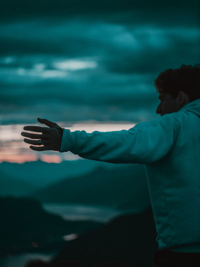 Man raising hand on sunrise background