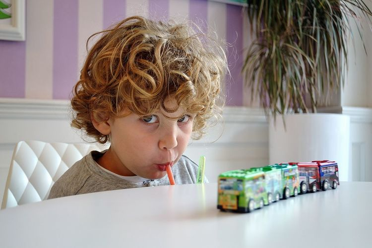 Portrait of boy drinking while sitting on table at home