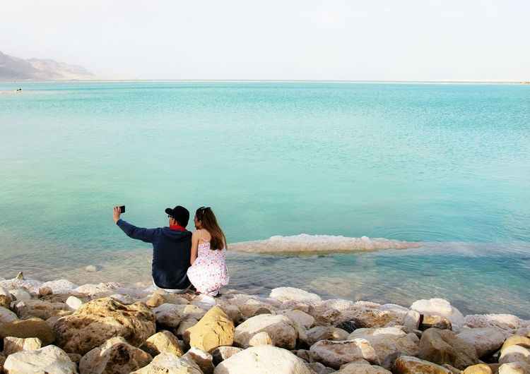 Couple clicking themselves with camera phone against the sea