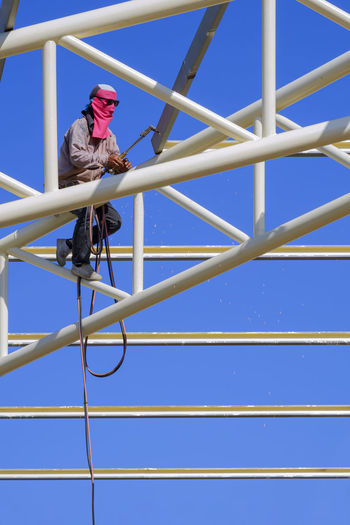 Low angle view of man standing on metallic structure against clear blue sky