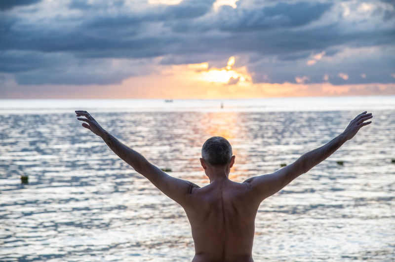 Rear view of man standing at beach against sky during sunset