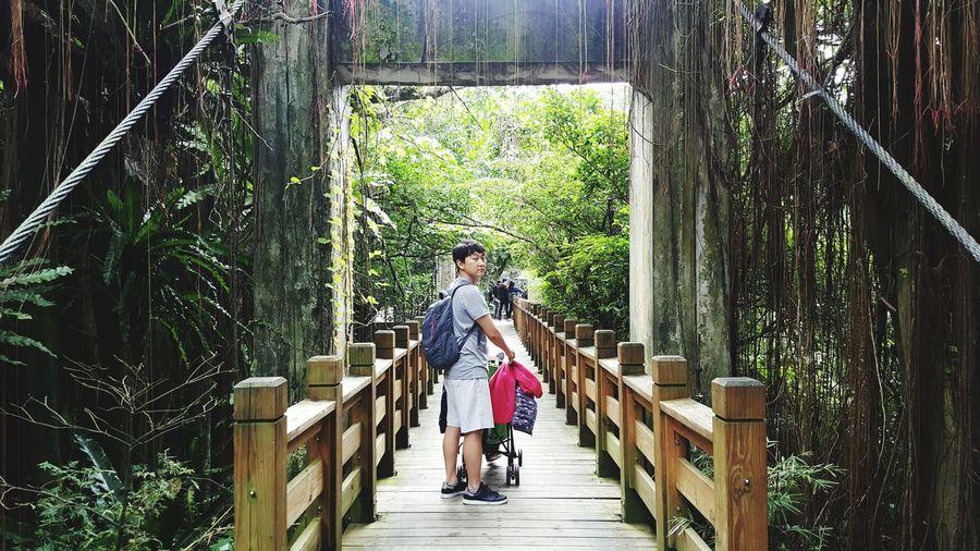 Young man standing on wooden footbridge