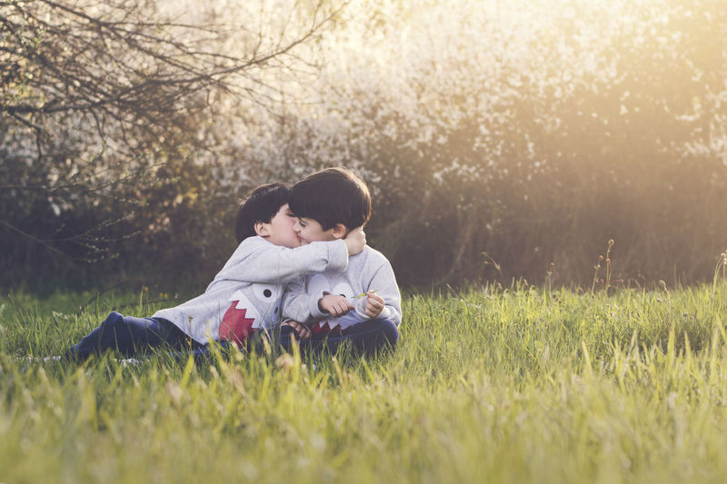 Complicity Friends Fun Funny Happiness Holidays Hug Love Boys Brothers Child Embrace Family Field Friendship Grass Innocence Nature Secrets Sibling Smiles Spring Springtime Twins Two People