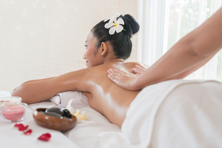 Smiling young woman being massaged by massage therapist in spa