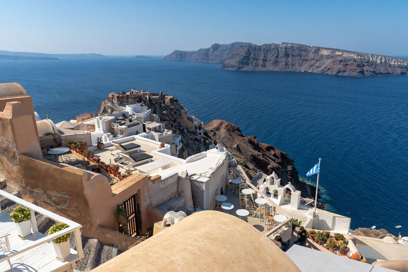 View of Oia - Santorini Cyclades Island - Aegean sea - Greece Greece Santorini Oia Cityscape Cyclades Island Mediterranean  Luxury Water Sea High Angle View Mountain Architecture Nature Built Structure Building Exterior Building Travel Destinations No People Sunlight Mountain Range Scenics - Nature Outdoors Religion Blue