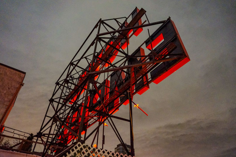 Low angle view of red crane against sky at dusk