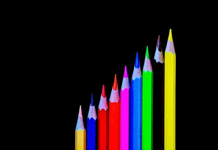 Close-up of multi colored pencils against black background
