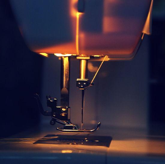 Close-Up Of Illuminated Sewing Machine In Darkroom