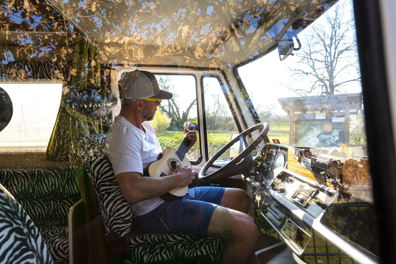 Side view of man playing guitar while sitting in bus seen through window