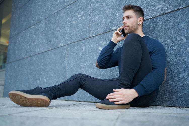 Young man using mobile phone while sitting on wall