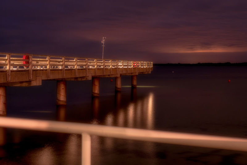 Illuminated pier over river against sky at sunset