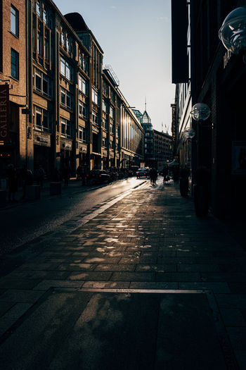 Empty road amidst buildings against sky in city
