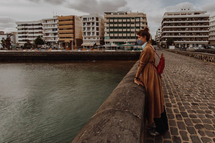 Woman standing in front of buildings against sky in city