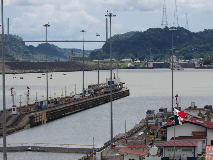 Sailboats on bridge over river against sky