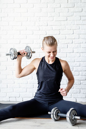 Healthy lifestyle. sport and fitness. young athletic woman working out with dumbbells