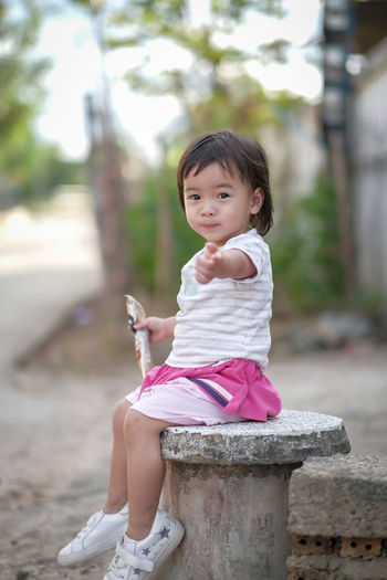 Portrait of a girl sitting outdoors