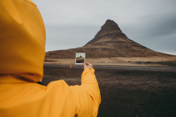 Rear view of man holding yellow camera against sky