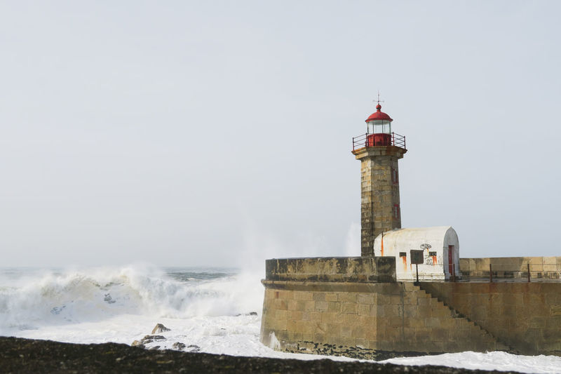 lighthouse farol das felgueiras with high waves of the atlantic ocean in porto, portugal Atlantic Ocean Porto Portugal White Water Water Sea Lighthouse Beach Wave Crash Motion Water's Edge Protection