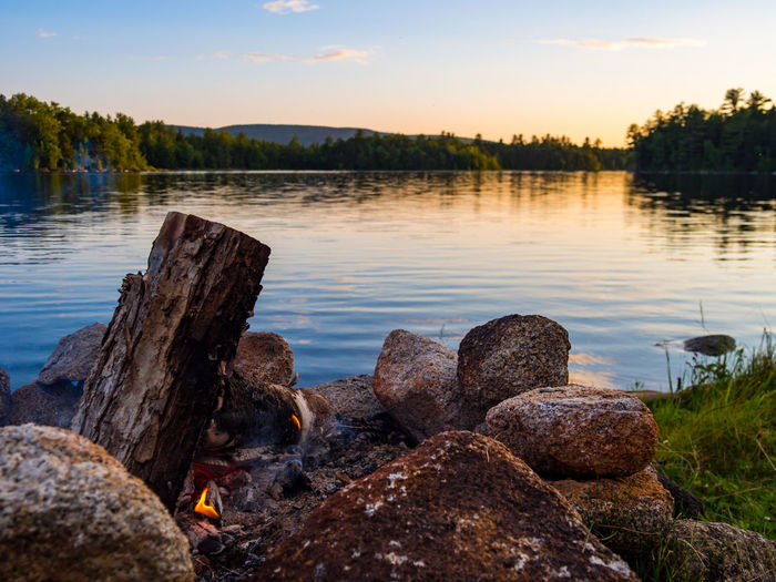 Rocks by lake against sky during sunset