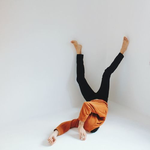 Man lying upside down against white background