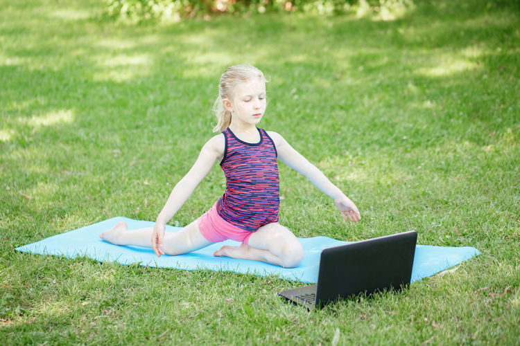 Cute girl exercising on field with laptop on grass
