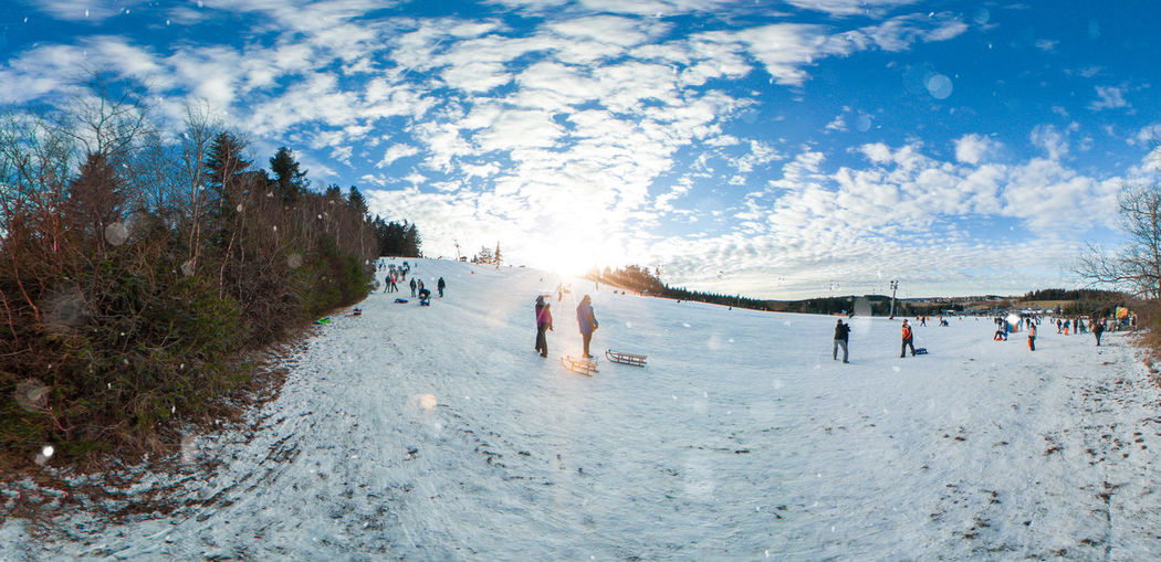 Tourists on snow land against sky during sunny day