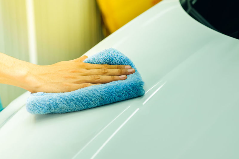 Cropped Hand Of Person Cleaning Car