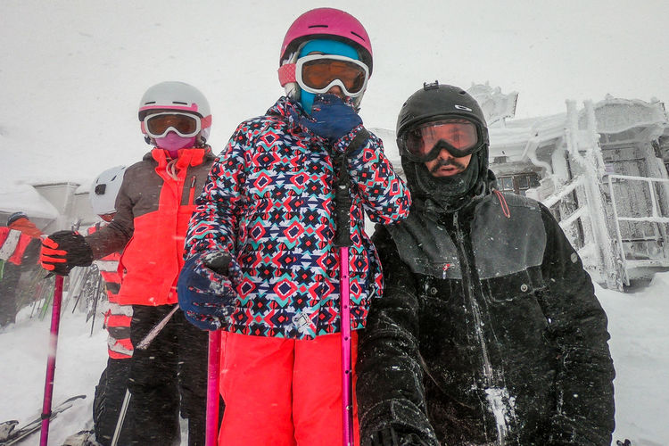 Father with daughters wearing ski wear during winter