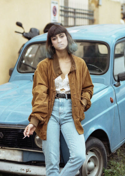 Portrait Of Woman Smoking Cigarette While Leaning On Car
