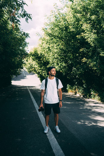 Full length portrait of young man standing on road