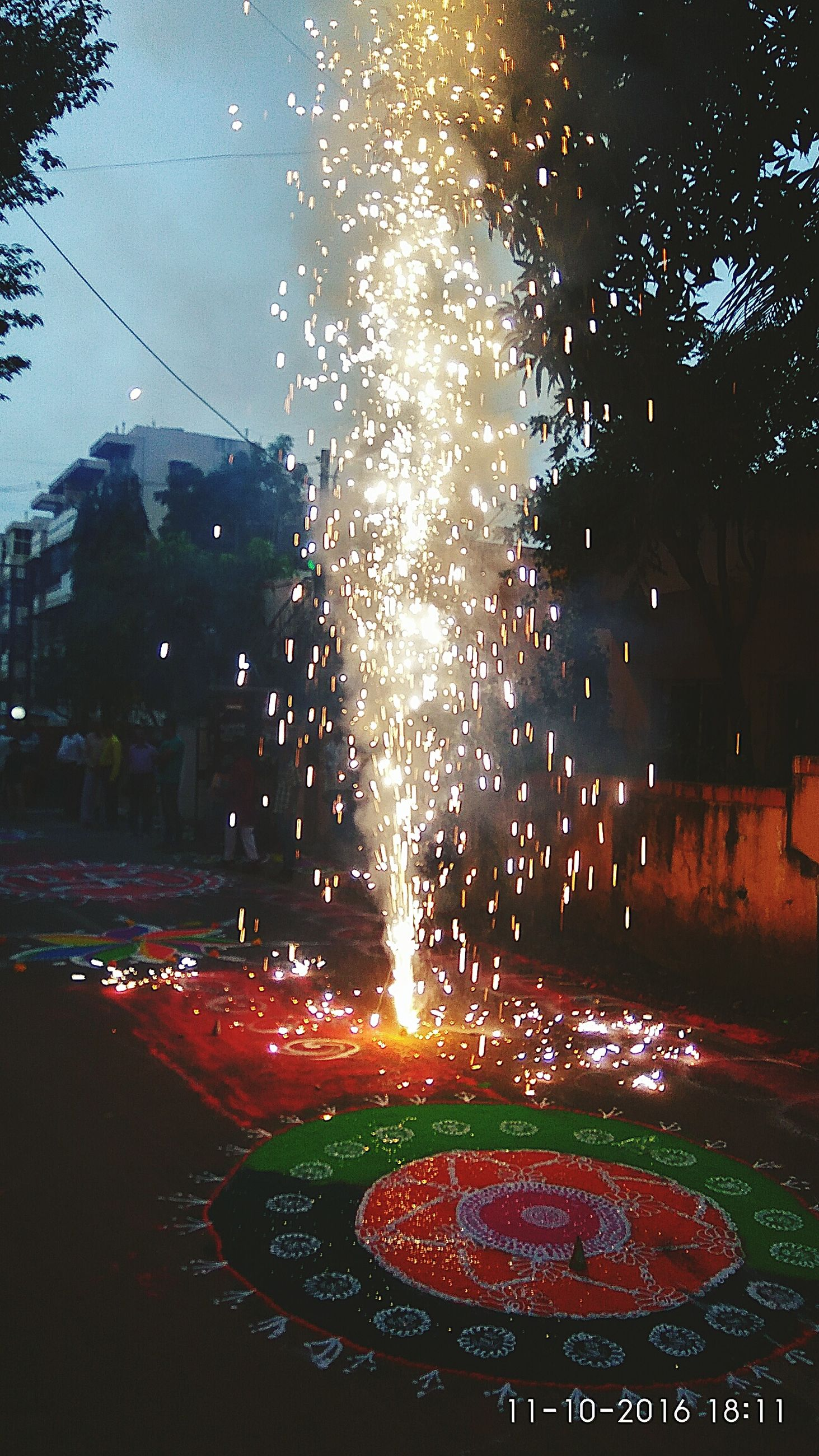 motion, long exposure, celebration, glowing, night, road, exploding, illuminated, firework display, light trail, blurred motion, sparks, event, red, firework - man made object, vibrant color, outdoors, entertainment, city life, sky, multi colored, tail light, lit, no people
