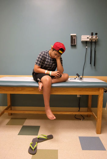 12 year old boy sitting on doctor's couch, looking sad, in a medical consultation room, Cancer Survivor Child Childhood Day Doctor  Doctors Appointment  Doctors Office Full Length Hospital, Wheelchair Human Body Part Indoors  Medical Medical Consultation Medical Treatment One Person People Red Cap Sad Sadness Sadness😢 Teenager Young Adult EyeEmNewHere