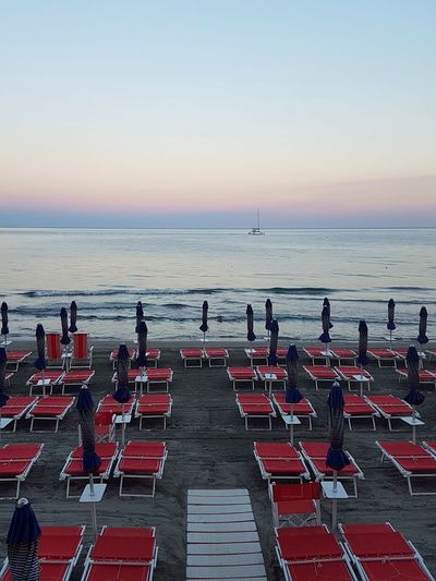 Beach Sea Horizon Over Water Sand Large Group Of People Water Chair Outdoors Arrangement Summer Sky Vacations Tranquility Nature Sunset People Day Beauty In Nature Sunset Sea Boat In A Row Tranquility Travel Destinations Liguria, Italy Beach Umbrella