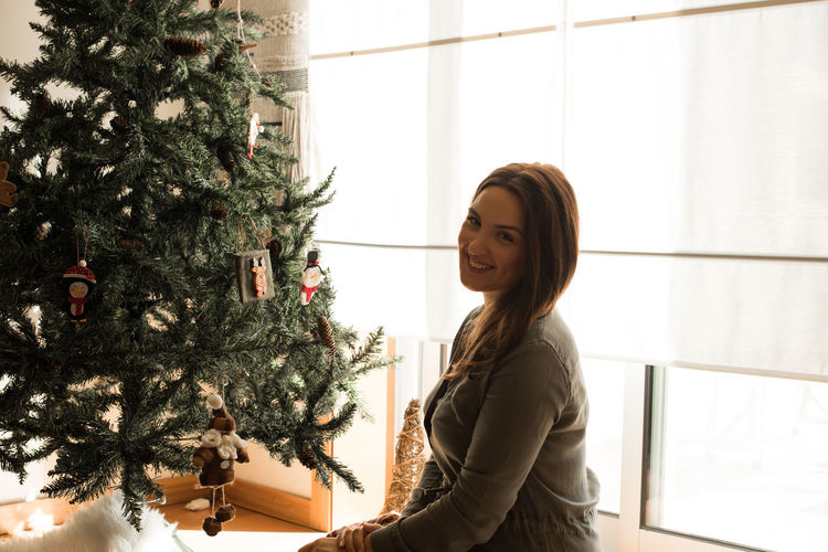 Portrait of smiling woman sitting by christmas tree at home