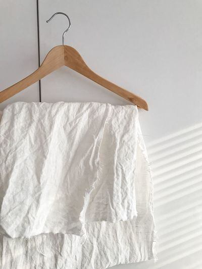 Close-up of clothes hanging against white wall