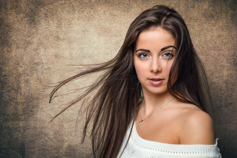 Portrait of beautiful woman against wall