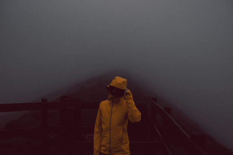 Woman wearing warm clothing during foggy weather