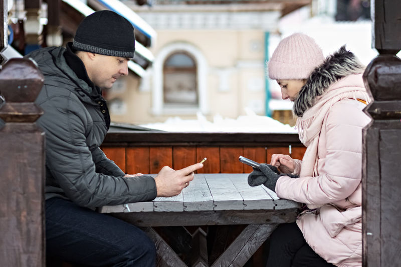 A couple is waiting for their order for lunch in a street cafe, texting by phone. communication