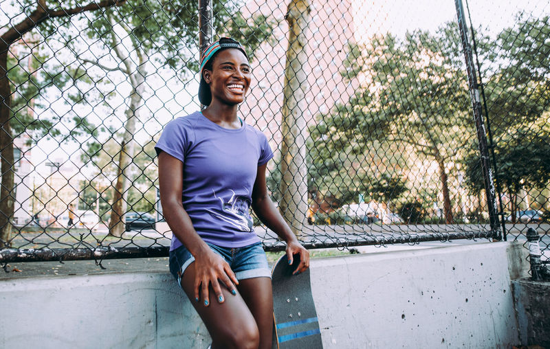 Portrait of smiling young woman standing against fence