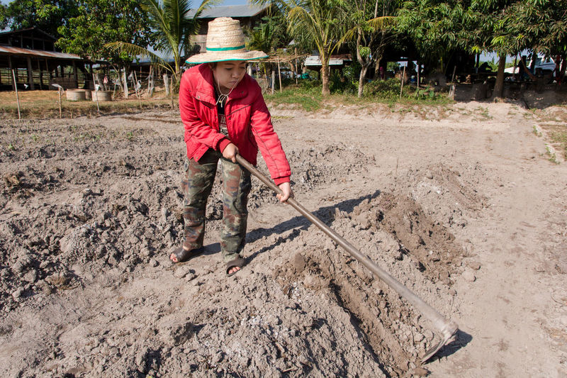 Female farmer wearing hat while working in farm