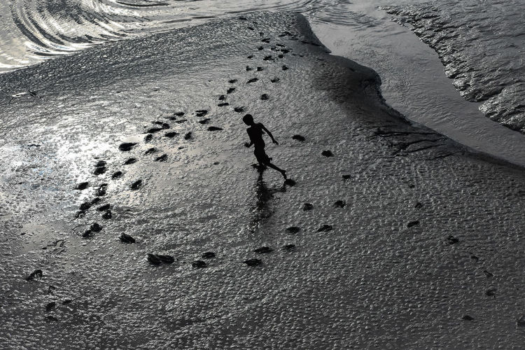 High angle view of man running on sand at beach